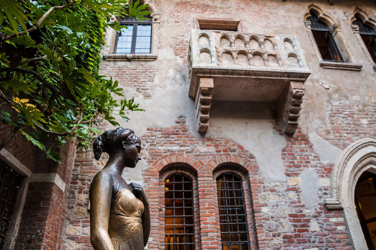 Statue of Juliet, with balcony in the background. Verona