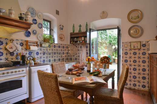 Villa di Citille - Kitchen both leading out to the courtyard with a loggia furnished for al fresco meals