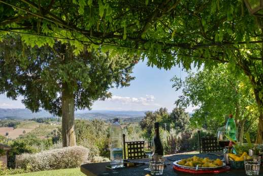 Podere Santa Giulia  - Shaded dining loggia set in the garden.