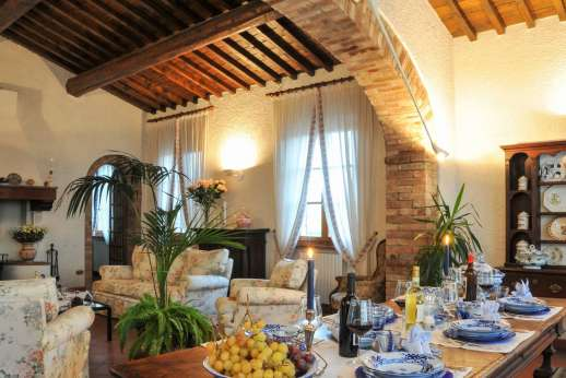 Villa Le Focaie - Spacious air conditioned living/dining room with an open fireplace.