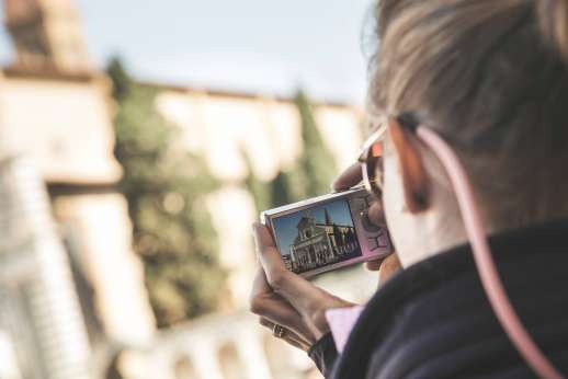 Arno Gondola Ride - A woman photographs the Basilica of Santa Maria Novella.