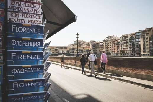 Arno Gondola Ride - A stack of tour guide books about Florence in multiple languages appear in a news stand while a tour group walk along the road by the Arno.
