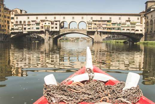 Arno Gondola Ride - A red gondola covered in chains floats away from the Ponte Vecchio bridge.