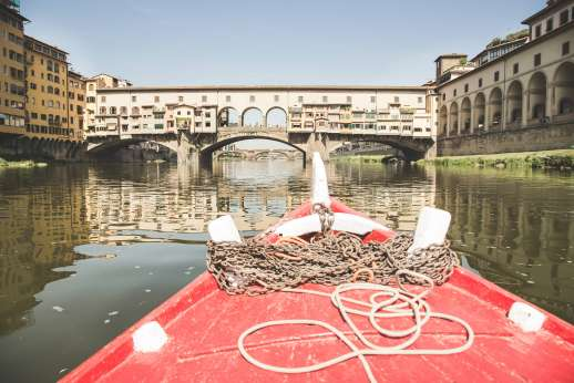 Arno Gondola Ride - A red gondola floats away from the Ponte Vecchio bridge on the river Arno.