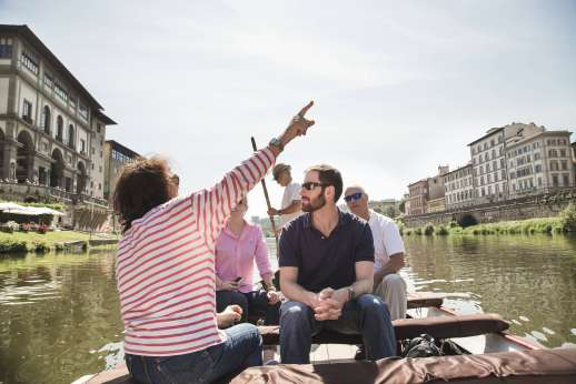 Arno Gondola Ride - A person points to a landmark during a gondola tour of the river Arno.