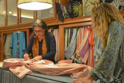 The Artisans of Florence - Women showing a piece of clothing to a visitor of the workshop in Tuscany