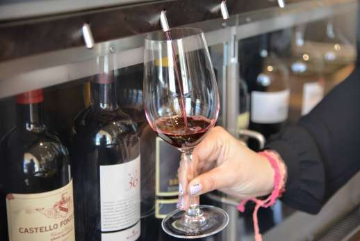 Chianti Wine Tour - A glass of red wine is poured in front of a selection of wine bottles.