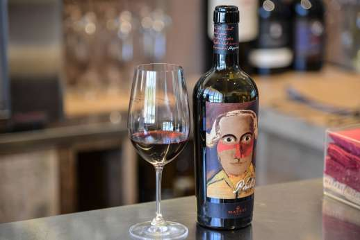 Chianti Wine Tour - A glass of red wine sits next to an open wine bottle bearing a painting of a man's face.