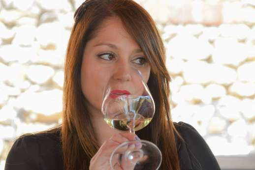 Chianti Wine Tour - A woman drinks from a glass of white wine as part of a wine tasting.