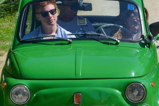 Fiat 500 Tour - Two people and a tour guide enjoy the sun in a green, classic Fiat 500.
