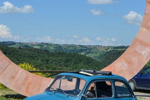 Fiat 500 Tour - A classic blue Fiat 500 with an open sunroof sits by a large, wheel-shaped monument overlooking the Chianti countryside