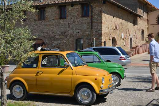Fiat 500 Tour - Two classic Fiat 500s parked next to a traditional Tuscan villa.