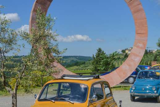 Fiat 500 Tour - Two classic Fiat 500s parked next to a large, wheel-shaped sculpture overlooking the Chianti countryside.