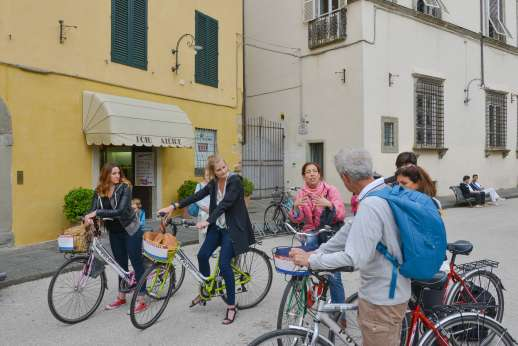 Lucca By Bike Or Foot - A tour group on bicycles stops to listen to their guide in the middle of Lucca