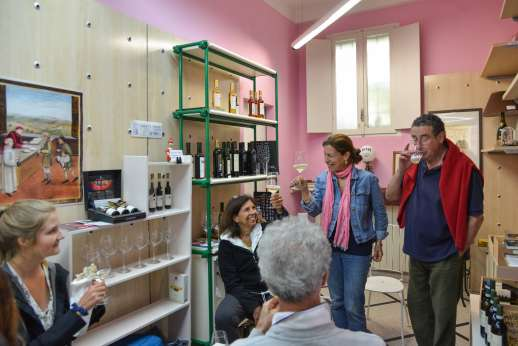 Lucca By Bike Or Foot - A tour group enjoy a wine tasting in a room with pink walls and paintings