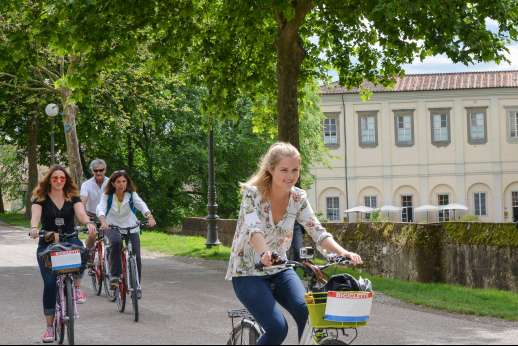 Lucca By Bike Or Foot - A group of people on rented bicycles cycle through a park in Lucca past an old building