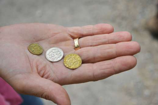 Lucca By Bike Or Foot - Antique coins in the palm of a hand.
