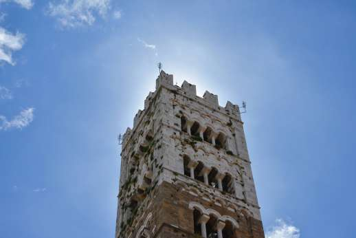 Lucca By Bike Or Foot - The top of an historic Italian tower eclipses the sun against a blue sky.