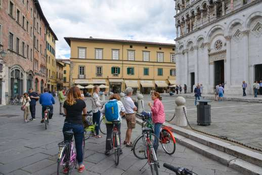 Lucca By Bike Or Foot - A group of tourists on bicycles stop to admire an historic building in Lucca.