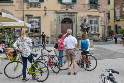 Lucca By Bike Or Foot - A tour guide stops the bicycle group to point out an old statue of a man in front of a building