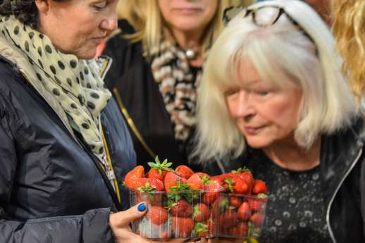 Florence Market Tour - A group of women inspects a plastic box of strawberries