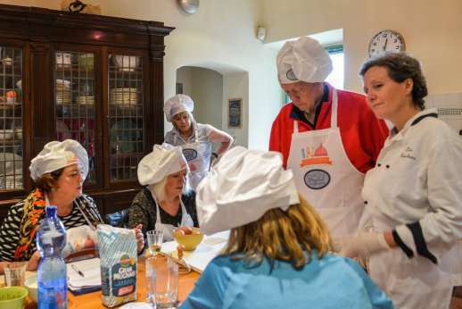 Florence Market Tour - A group of people in an Italian kitchen learning to cook with a chef.