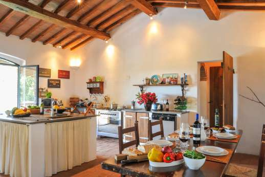 Campo Chinandoli - Large air-conditioned kitchen area with a fireplace and glass doors opening to a long, shaded balcony furnished for dining and lounging.