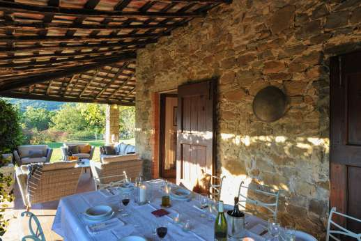 Casa al Bosco -  Shaded loggia with a dining table leading into the living room