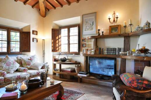 Casa Paggetti - Sitting room with a library and a decorative fireplace.