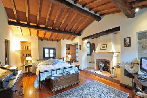 Casa Paggetti - The main double bedroom with walk in wardrobe and a decorative fireplace.