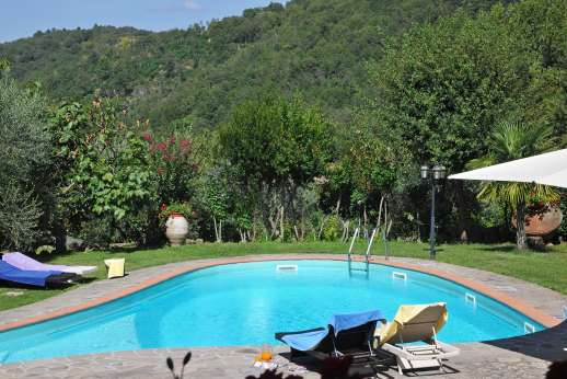 Casa Paggetti - Pool terrace, surrounded by lush lawns with sun loungers and an umbrella for shade.
