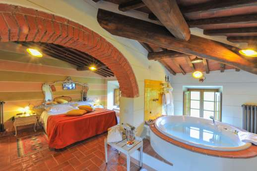 A Cooking Week at I Corbezzoli - The bed with the mirrored headboard in Gli Olivi. All bedrooms are air conditioned.