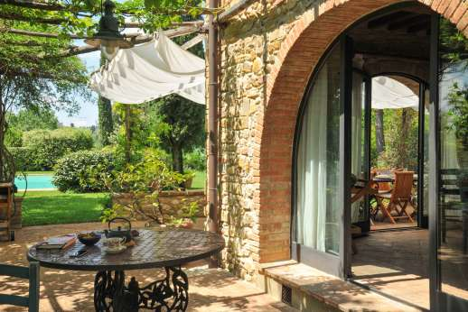 I Tre Cipressi - Seating under the pergola leading into the kitchen