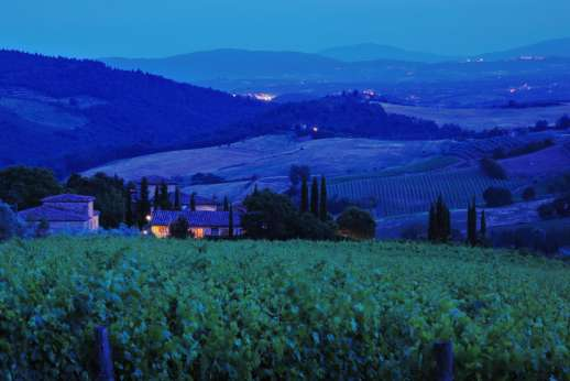 I Tre Cipressi - The view by night over the tuscan vineyards and hilltop villages.
