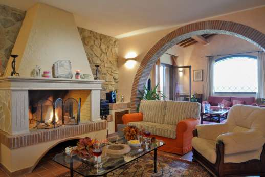 Il Chiesino - Ground floor sitting room with an open fireplace and French doors leading out to the two loggias.
