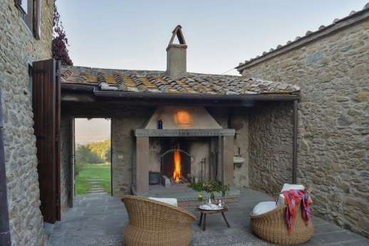 Il Cortile Pratolino - In the courtyard there is a wonderful little nook provides an outdoor sitting area in front of a big stone fireplace