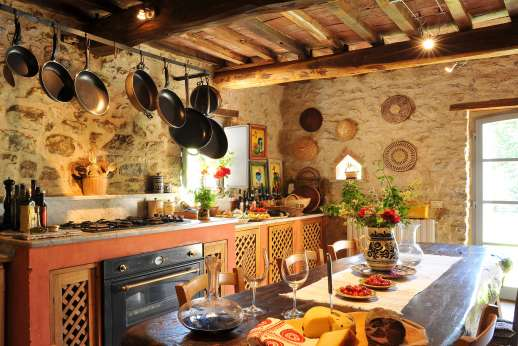Il Fienile - The well-equipped kitchen with a breakfast table leading into the garden.