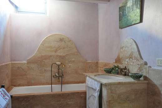Il Fienile - A marble bathroom with bath.