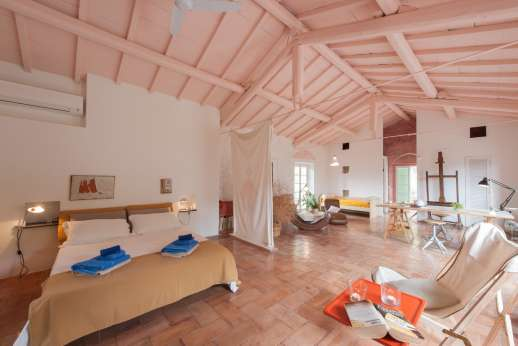 Isola Rossa - The first floor bedroom is accessed by an external staircase. With high ceilings stretching the length of the villa, this is a fantastic place to spend your time.