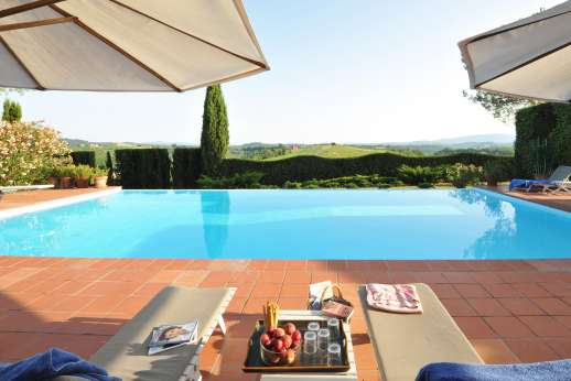 La Casa Rossa - The pool terrace furnished with sunloungers and umbrellas.