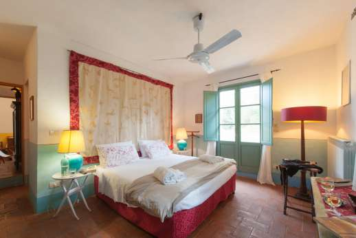 La Magione - Double bedroom with an en suite bathroom with bath and glass doors opening to the garden facing the swimming pool.