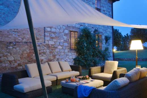 La Piana - The seating area between the villa and pool house, perfect for relaxing outdoors in the evening.