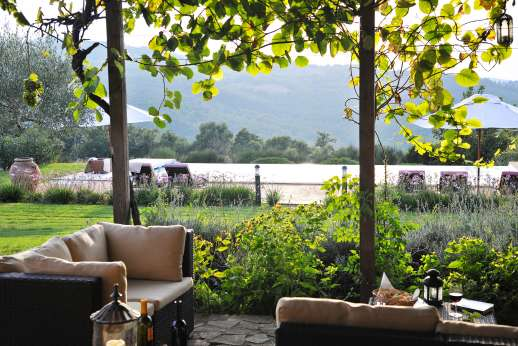 La Pianstella - A large loggia with garden furniture and a dining table facing the valley.