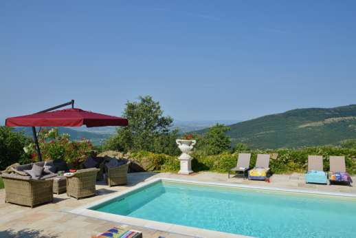 Le Bruciate - Seating area by the pool enjoys spectacular views of Tuscany.
