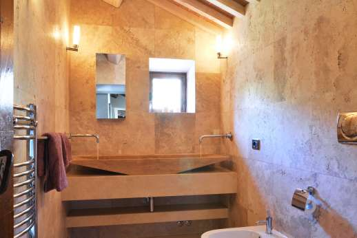Le Bruciate - The Travertine bathroom with large wash basin is shared by the two doubles bedrooms on the first floor.