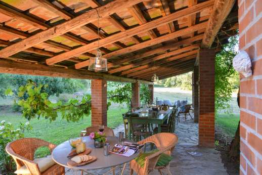 Pergoletto - Garden loggia with a long dining table and a sitting area.
