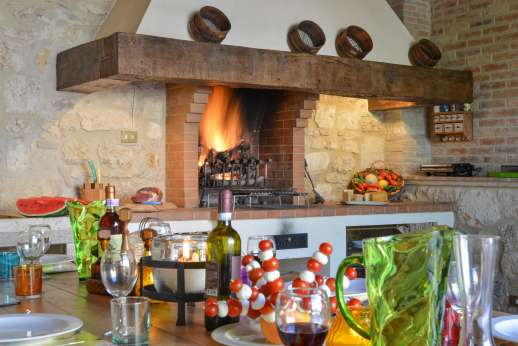Podere Casalfava - Summer kitchen with seating area and open fire