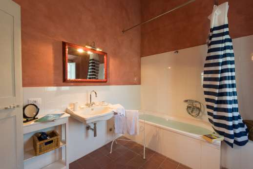 Podere Castelluccio - An en suite bathroom with bath.