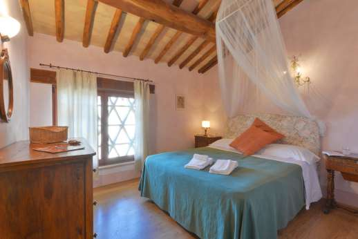 Podere Celli - Air conditioned double bedroom [US California King size] with ensuite bathroom with bath.