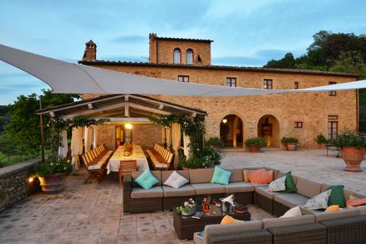 The large paved terrace with seating area and loggia by dusk